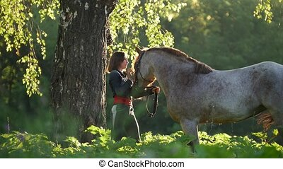 Girl rider stands with a horse near a tree against a green...