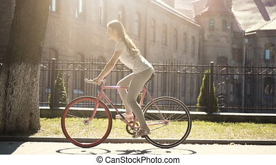Girl Rides a Bike - Long-haired slim brunette cycling in the...