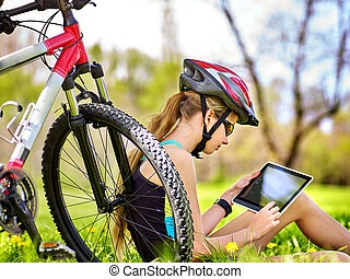 Girl rides bicycle wearing headset cycling watch in pc tablet.