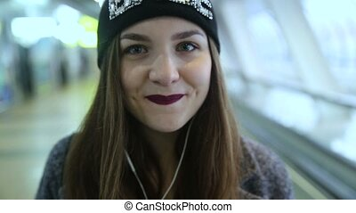 Girl rides on travelators and smiling