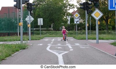 Girl rides the bike at playground traffic. Little girl on...