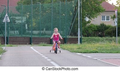 Girl rides the bike at playground traffic. Little girl on bike in the summer