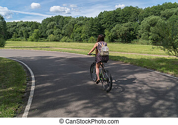 Girl riding a bicycle. Back view. Forest and clouds in the background