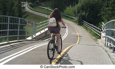 Girl riding a bicycle. Side view. Forest and clouds in the background