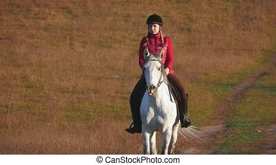 Girl riding a horse walking in the meadow. Slow motion