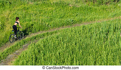 Girl riding a mountain bike in the field