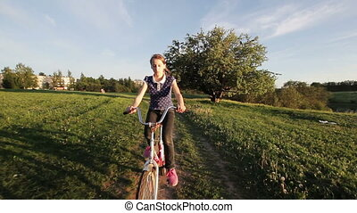 Girl riding bicycle in the countryside