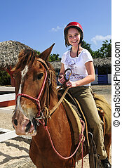 Girl riding horse - Young girl riding brown horse wearing...