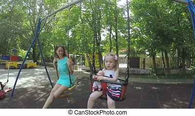 Girl riding on a swing mom