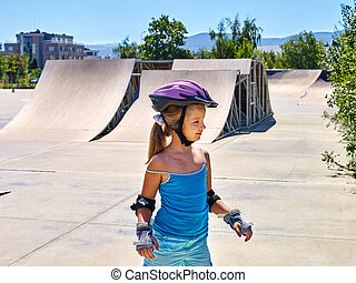 Girl riding on roller skates in skatepark. Outdoor.