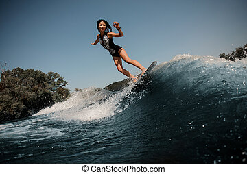Girl riding on the wakeboard on the lake