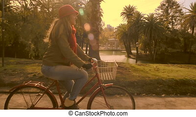 Girl riding retro bicycle on autumn day at park - Young...