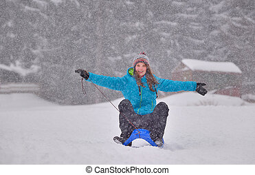 girl riding sled down snow slope