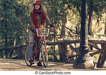Girl riding vintage bike on fall season at park