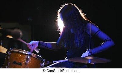 Girl rock musician - female drummer performing, slow-motion