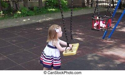 Girl rocking doll in park