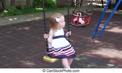 Girl rocking doll in park - The park girl shakes on a swing...