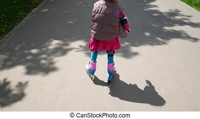 Girl rollerblading on the avenue of the park.