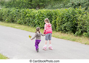 girl rollerblading, with a little sister, outdoors