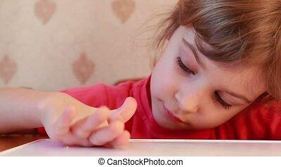 Girl rolling plasticine ball on table - beautiful girl...