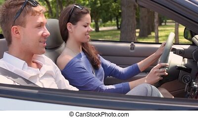 Girl rotate wheel in cabriolet and boyfriend is near