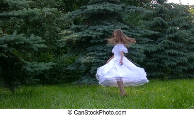 girl rotating in park with grass and conifers