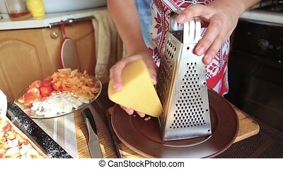 Girl rubs cheese in the kitchen