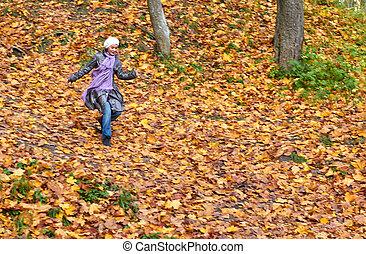 girl run in bright yellow autumn forest