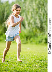 girl running and jumping on grass