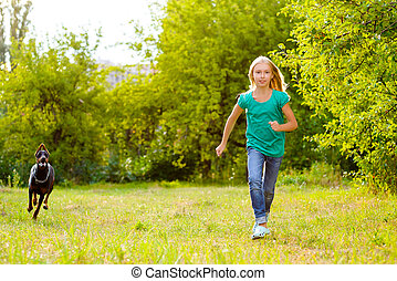 girl running away from dog or doberman in summer park