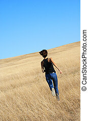 Girl running away in a field