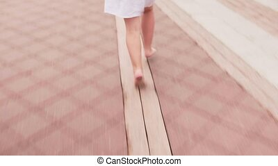 Girl running barefoot on city street in white dress - Little...