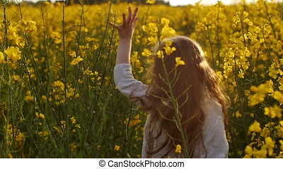 Little girl stands and then begins to run cross the flowers field at sunset. close-up. Slow motion.