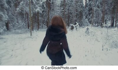 Girl running in the winter forest. She turns, whirls and...