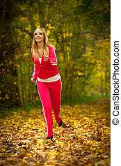 Girl running jogging in autumn park