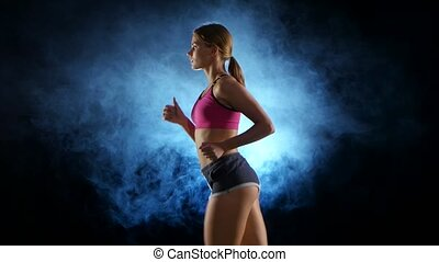 Girl running on a black background illuminated by the spotlight in the smoke. Close up