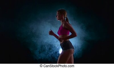 Girl running on a black background illuminated by the spotlight in the smoke. Slow motion. Close up