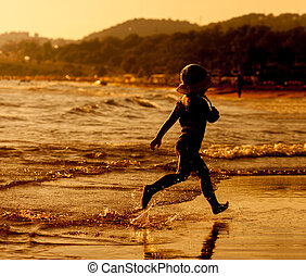 Girl running on beach at sunset.