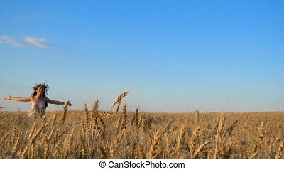 girl running on golden wheat field and touching ripe ears