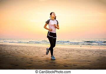 Girl running on the beach at sunset