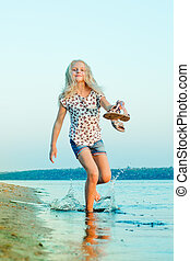 girl running on the beach at the water barefoot