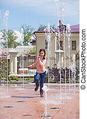 Girl running through the water jets in a fountain.