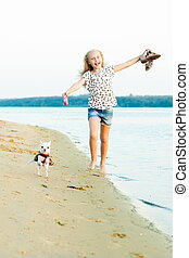 girl running with a dog on the beach