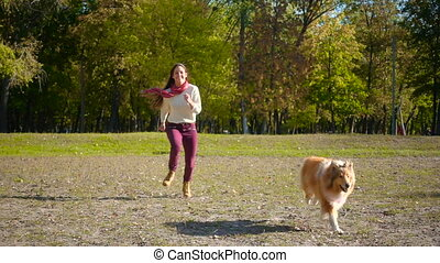 girl running with collie dog at autumn park