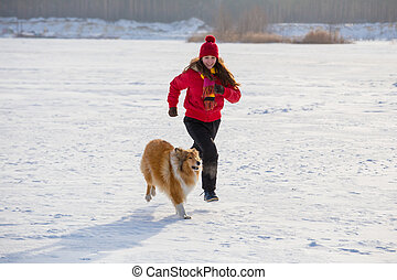 Girl running with collie dog at winter landscape