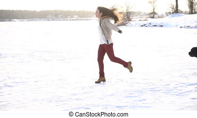 girl running with dogs on winter snow field - Young girl...