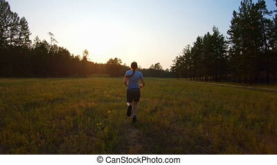 Girl runs across the field at sunset