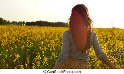 girl runs arms outstretched through a field slowmo - young...