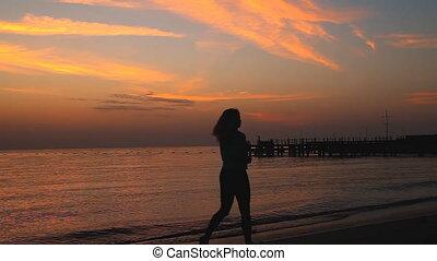 Girl runs at dawn along the seashore - Silhouette of a young...