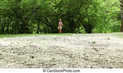 Girl runs closer from far across meadow all strewn fluff
